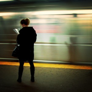 Woman reading on train platform.